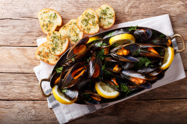 Copper pot of gourmet mussels with lemon