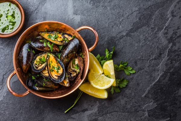Mussels in copper bowl with lemon and herbs