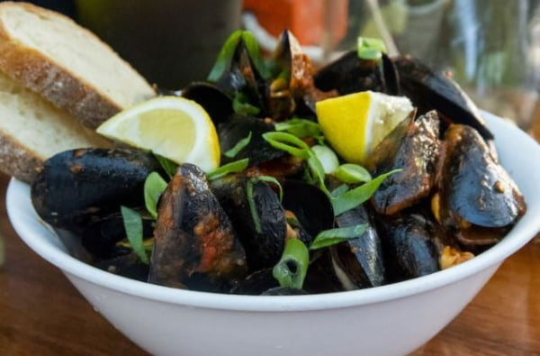 Mussels in a bowl with lemon and bread