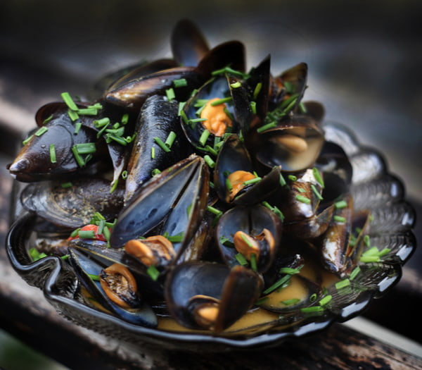 Plate of mussels in seafood sauce in the foreground