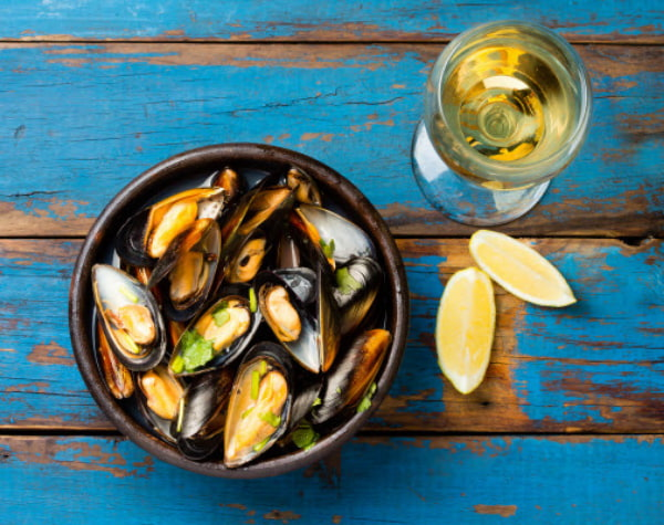 Mussels on a pot with a glass of wine and a lemon on the table