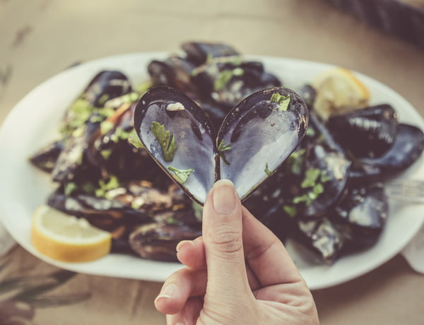 Female hand holding opened heart shaped mussel