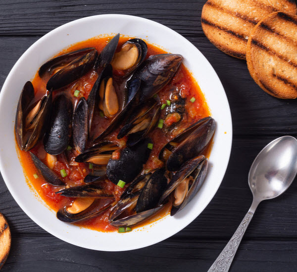 Mussels with Tomato soup with bread and spoon beside