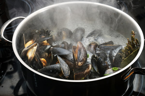 Steaming blue mussels in a steel pot with boiling broth