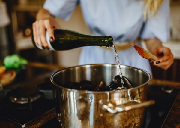 Girl adding white wine to a pan with mussels