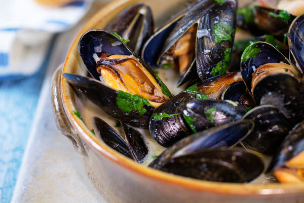 Steamed Mussels with wine served in a pot on the table