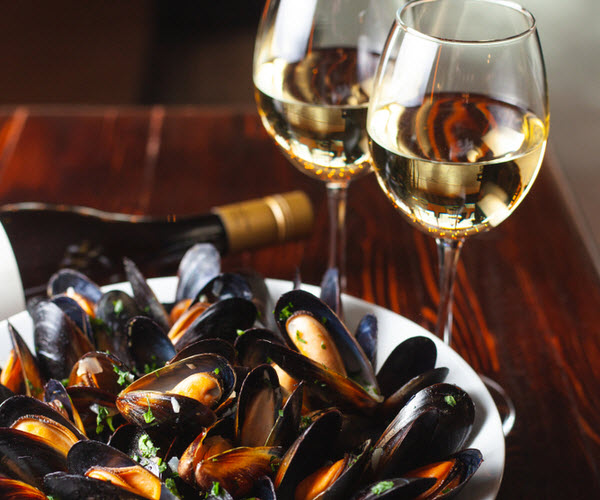 steamed mussels and white wine served on the table