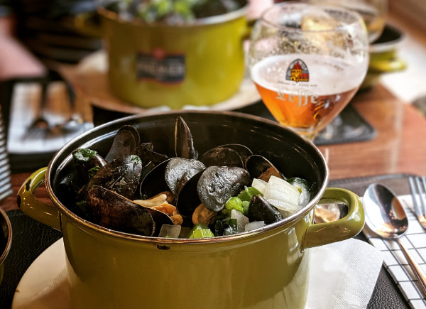 Cooked Mussels in a pan served with beer