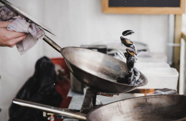 Hands holding the pot with mussels