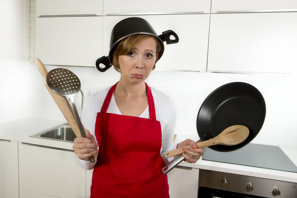 Woman in red apron at kitchen holding pan