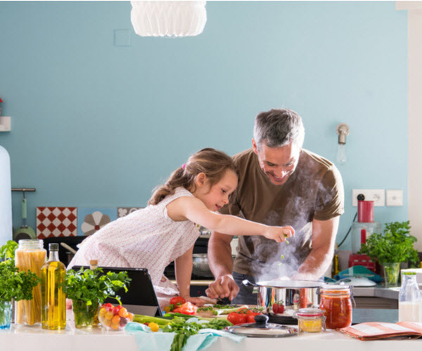 Father and daughter cooking at home