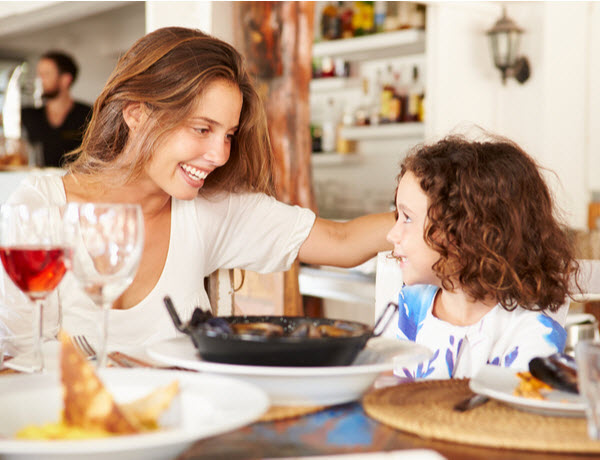 Mother and daughter eating a delicious meal at the restaurant